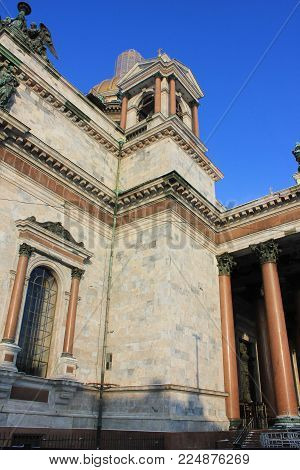 Saint Isaac's Cathedral in St. Petersburg, Russia. Neoclassical Historic Architecture Low Angle Detailed View of Granite Building, Colonnade Pillars and Sculptures against Blue Sky on Sunny Day.