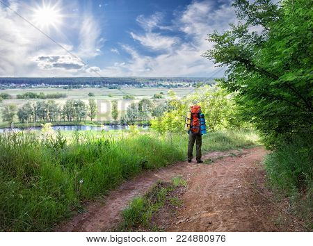 Tourist standing on the road atop hill. A tourist with backpack is standing on country road passing through hill above the river. Summer landscape. The concept of freedom and travel.