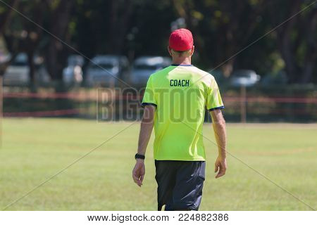 back of a coach wearing bright green color shirt with the word Coach written on, walking with blur outdoor sport field background