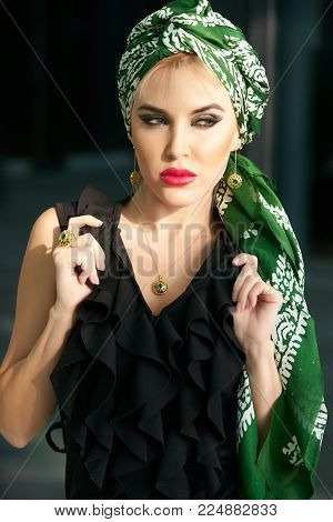 Beautiful elegant blonde woman posing in black dress and green oriental scarf, close-up portrait. Indoor studio shot.