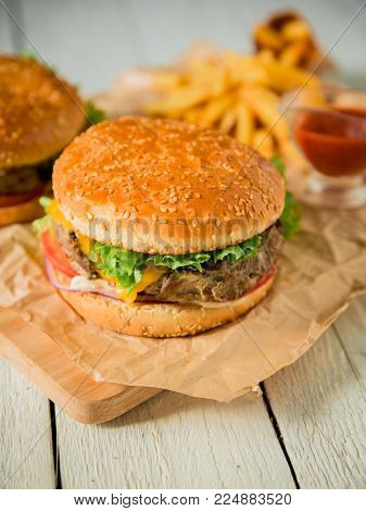 Burger with beef, salad, sauce and tomato on wooden table. American fact food