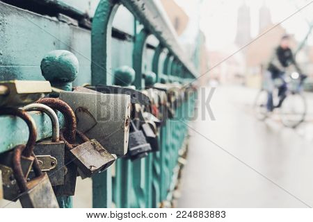 Symbolic love padlocks fixed to the railings of Tumski bridge in Wroclaw, Poland. Shallow depth of field, view on the city