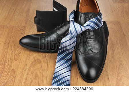 Classic mens black shoes, tie, purse, on wooden floor. Men's fashion and lifestyle.
