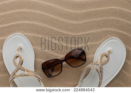 Luxury, decorated with rhinestone beach flip flops and sunglasses, lying on sand dunes