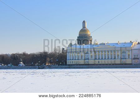 Saint Isaac's Cathedral and Historic Architecture Buildings Winter View in St. Petersburgi, Russia. Frozen Neva River Covered in Snow on Bright Sunny Day on Winter Seasonal Background with Copy Space.