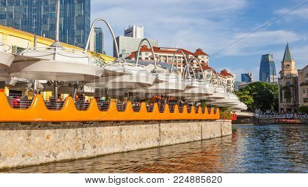 CLARKE QUAY, SINGAPORE - AUGUST 17, 2009: Diners at a colorful restaurant at Clarke Quay on the Singapore River, with skyscrapers in the background.