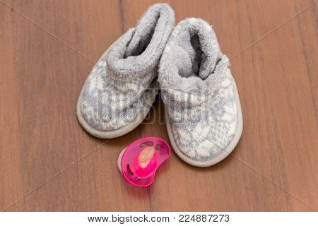 Baby booties and soother on wooden background