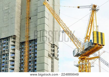 Construction Site. Big Industrial Tower Cranes With Unfinished High Raised Buildings And Blue Sky In