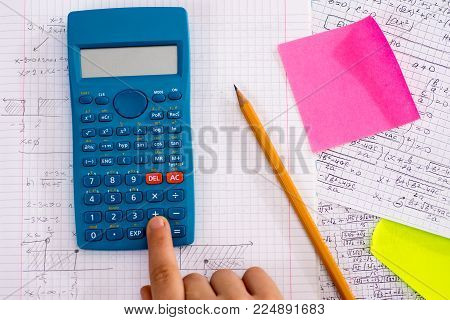 Finger on the Calculator Button During Mathematical Lesson. School Concept.