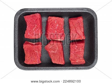 Pieces of fresh raw beef meat in plastic tray on white background