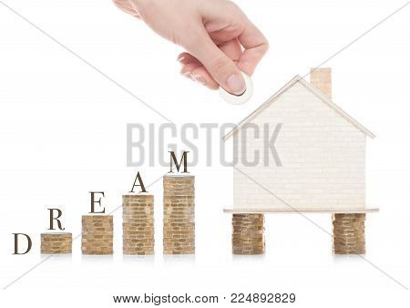 Wooden house model standing on coins and hand holding the coin with conceptual text. Dream