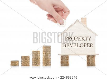 Wooden house model standing on coins and hand holding the coin with conceptual text. Property Developer