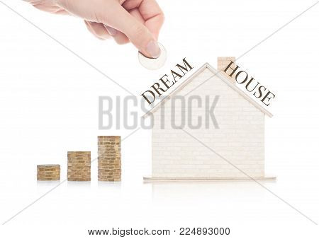 Wooden house model with coins next to it and hand holding the coin with conceptual text on top of the roof. Dream House