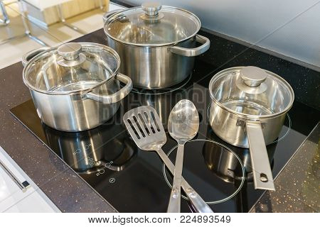 Metal Pot and pan on induction hob in modern kitchen. modern kitchen pot cooking induction electrical stove hob concept