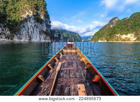 wooden longtail boat trip adventure at Ratchaprapa dam, Thailand