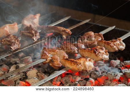 Cooking of a meat on grill on metal skewer