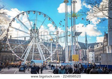 APRIL 2015, AMSTERDAM NETHERLANDS: Dam square in Amsterdam with ferris wheel of amusement luna park in centre