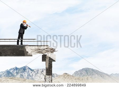 Young engineer in suit and helmet looking in spyglass while standing on broken bridge with skyscape and nature view on background. 3D rendering.