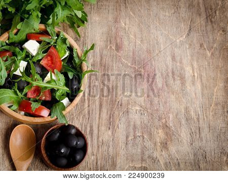 Salad with tomatoes and olives on wooden background.bunch arugula, a bowl of olives, a bowl of salad and a wooden spoon with one hand with the other place for your text