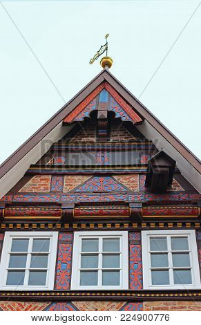 gable of a beaufitul restorated half-timbered house with multi colored decorative elements, in Germany