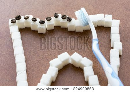 The toothbrush cleans the white tooth from the coffee plaque