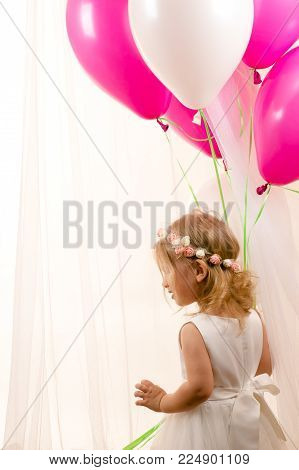 beautiful little girl holding balloons at birthday party