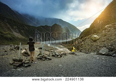 tourist taking a photograph at fox glacier trekking trail most popular traveling destination in west coast southland new zealand