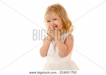 shy little baby in white dress isolated on white background