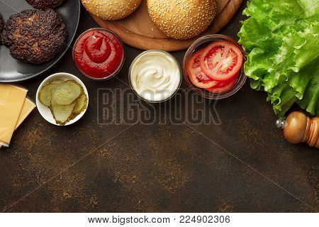 Burgers ingredients for cooking homemade snacks with copy space top view. Concep of junk food.