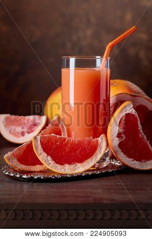 Glass Of Fresh Grapefruit Juice And Cut Fruits .