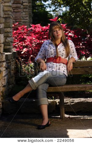 Pretty Teenage Girl Sitting On Bench