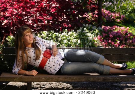 Teenage Girl Lying On A Park Bench