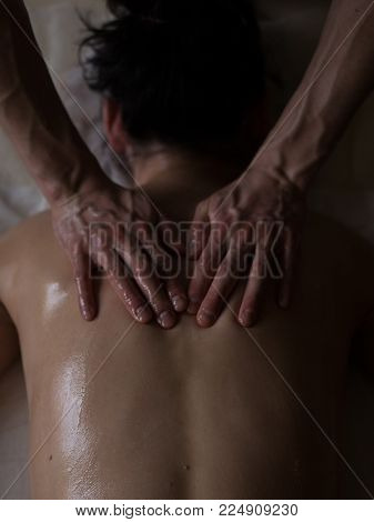 Ayurveda Massage concept. Beautiful young woman reciving relxing Massage of Her Back from Professional Masseur