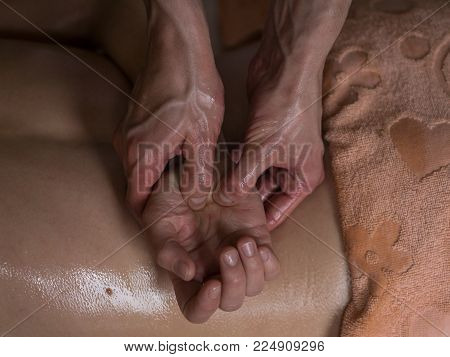 Beautiful young woman reciving relxing Massage of Her Oiled Palm from Professional Masseur. Close up