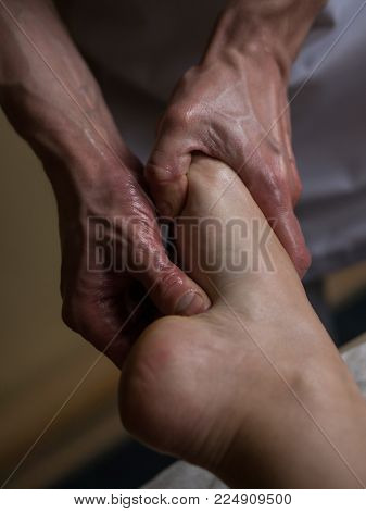 Beautiful young woman reciving relxing Foot Massage from Professional Masseur. Close up