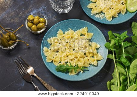 The pasta is sprinkled with cheese served on blue plates with arugula, olives and pickled capers.Italian food.