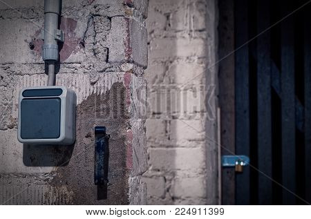 Cellar with a padlock and a cellar door in a tenement with a light switch in blue optics