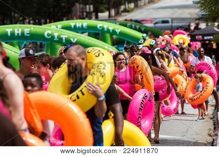 ATLANTA, GA - JULY 2017:  Hundreds of people carry innertube floats as they get in line to participate in Slide the City, a giant tubing water slide set up on a hilly street in downtown Atlanta in Atlanta, GA on July 15, 2017.