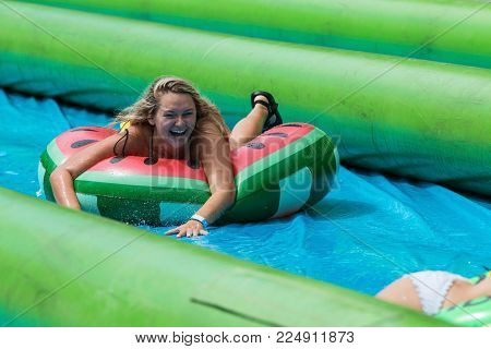 ATLANTA, GA - JULY 2017:  A young woman laughs as she travels down a giant slip-and-slide in an innertube, at the Slide The City event in Atlanta, GA on July 15, 2017.