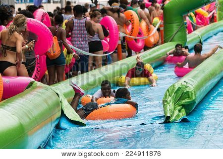 ATLANTA, GA - JULY 2017:  People carrying innertubes stand in a long line waiting their turn and watch others slide downhill at the Slide The City event, in Atlanta, GA on July 15, 2017.