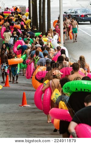 ATLANTA, GA - JULY 2017:  Dozens of people stand in a long line holding innertubes and waiting for their turn at Slide The City, a huge slip and slide event in Atlanta, GA on July 15, 2017.