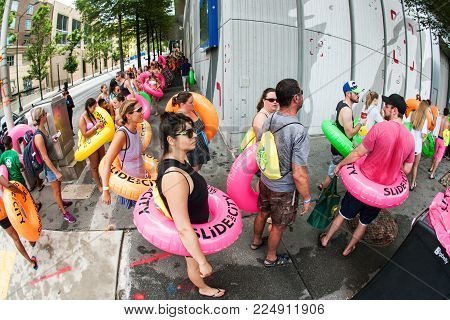 ATLANTA, GA - JULY 2017:  People carrying innertubes stand in a long line stretching around a city block, waiting for their turn on the water slide at the Slide The City event, in Atlanta, GA on July 15, 2017.
