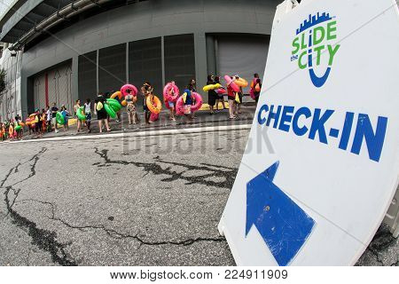 ATLANTA, GA - JULY 2017:  People carrying innertubes stand in a line stretching around a city block, waiting for their turn on the water slide at the Slide The City event, in Atlanta, GA on July 15, 2017.