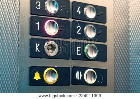 Elevator knobs with yellow help button and numbering from the ground floor to the 3rd floor