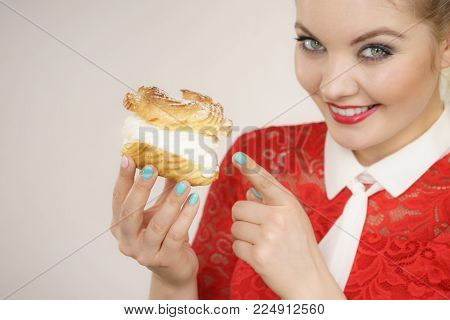 Sweet food and happiness concept. Funny joyful blonde woman holding yummy choux puff cake with whipped cream, excited face expression. On grey