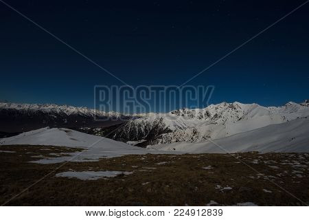 Starry sky night view on the Alps. Snow capped mountain range in moonlight.