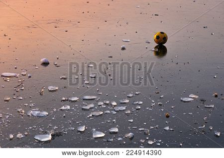 On the background of a pink-orange sunset, a yellow ball is an interesting and curious object on the frozen lake, accompanied only by pieces of ice.