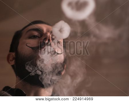Young Man with Beard and Mustages Vaping an Electronic Cigarette. Vaper Hipster Smoke Vaporizer and Exhals Smoke Rings. 4k UHD