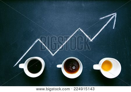 Cups of coffee under the trend line. Move up of energy. Trend up of energy. Arrow and graph. Coffee on a blackboard. Concept of energy