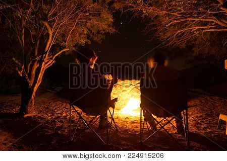 Couple sitting at burning camp fire in the night. Camping in the forest under starry sky, Namibia, Africa. Summer adventures and exploration in the african National Parks. Selective focus on fire. Toned image.